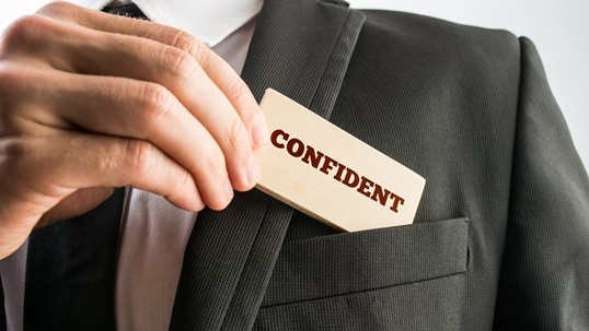 Businessman removing a wooden card reading Confident from the pocket