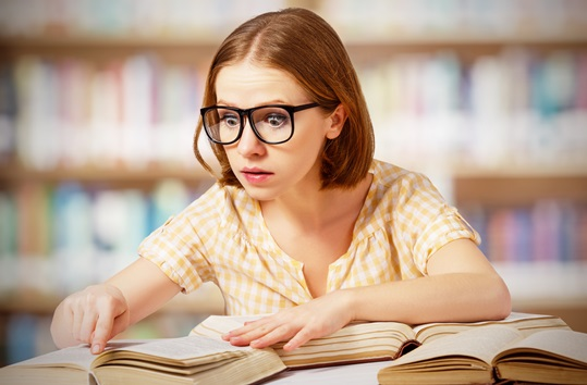 funny surprised girl  with glasses reading books