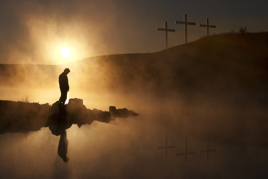 Dramatic religious photo illustration of Easter Sunday Morning reflecting a prayerful moment of silence with a silhoutted person bowing his head, a warm sunrise rises over a foggy lake, and three crosses appear as a vision on a hill, reflected in the water as well.