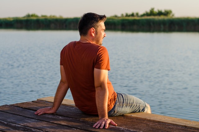 Young man sitting relaxing and enjoying the view from dock