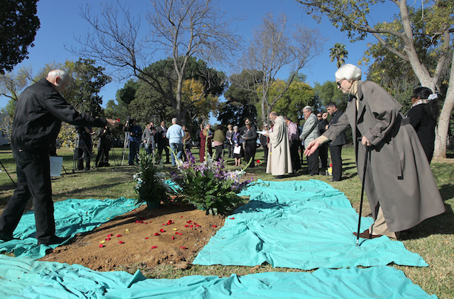This photo from December 2013 - People scatter rose pedals during an interfaith graveside memorial service.in Los Angeles, California. (Photo by David McNew/Getty Images)